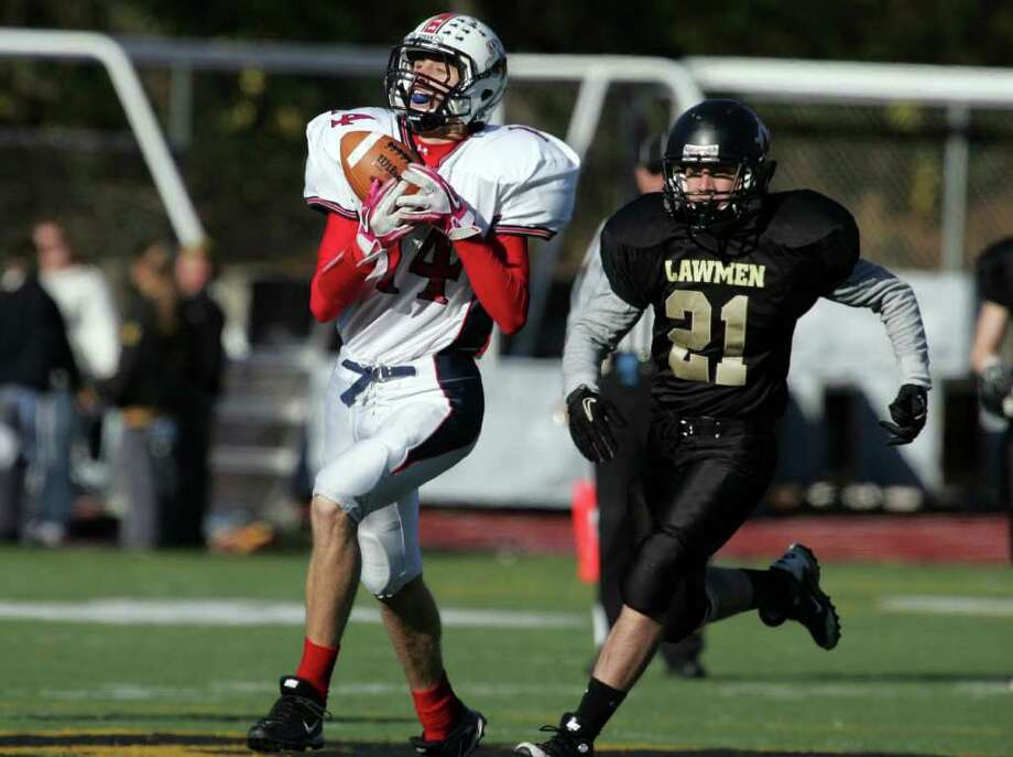 Foran High School's # 14 Jeffrey Raucci hauls in a reception as Jonathan Law High School #21 Kenny Bourque gives chase during first half action during Thanksgiving Day Match-up at Jonathan Law High in Milford. Foran would win 48-13. Photo: Mike Ross / Connecticut Post freelance
