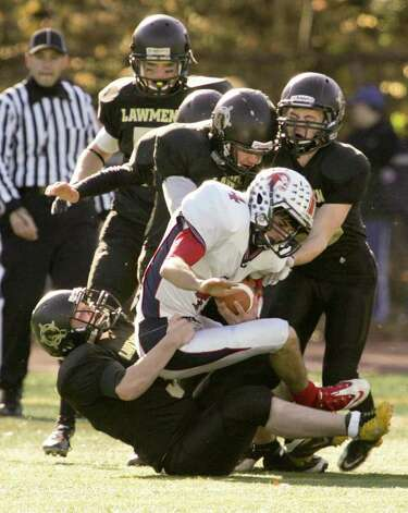 Foran High School's quarterback # 4 Matthew Aspinwall hits a wall of Jonathan Law High School defenders ( #39 Mark Thibault, # 55 George Knoth, # 16 Matt Ferraiolo , # 21 Kenny Bourque and # 80 Cody Edson during first half action on Thursday. Foran High School would win 48-13 on the Thankgiving Day Match-up. Photo: Mike Ross / Connecticut Post freelance