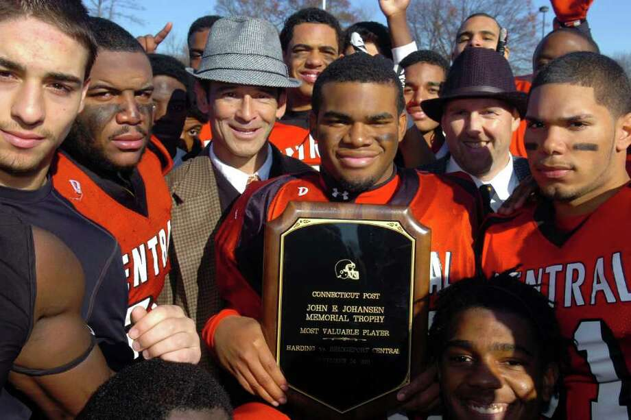 Central's Frederick Tuker, seen here with head coach Dave Cadelina and his team mates, holds the John E. Johansen Memorial Trophy following Central's victory over Harding on Thanksgiving, Nov. 24th, 2011. Photo: Ned Gerard / Connecticut Post