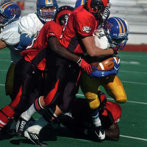 Harding's Taquan Broadway is tackled by Central defenders during Harding vs. Central high school football action at Kennedy Stadium, Central High School, in Bridgeport, Conn. on Thanksgiving, Nov. 24th, 2011. Photo: Ned Gerard / Connecticut Post