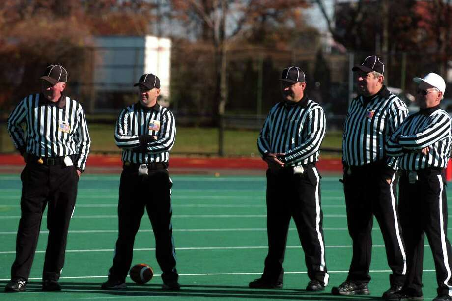 The officiating crew stands by during an injury break during Harding vs. Central high school football action at Kennedy Stadium, Central High School, in Bridgeport, Conn. on Thanksgiving, Nov. 24th, 2011. Photo: Ned Gerard / Connecticut Post