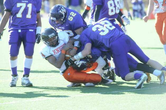 Stamford's Barry Boderick is tackled by Westhill's David Engel, right, and Seamus Ronan as Westhill High School hosts Stamford High for a crosstown battle on the football field on Thanksgiving Day, November 24, 2011. Photo: Keelin Daly