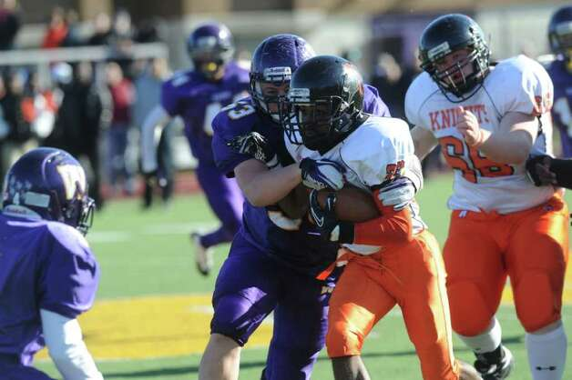 Stamford's Jamor Thompson pushes for yards as Westhill's Chris Soule moves in for the tackle as Westhill High School hosts Stamford High for a crosstown battle on the football field on Thanksgiving Day, November 24, 2011. Photo: Keelin Daly