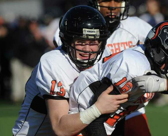Stamford's Chandler Foster hugs teammate Jake Demetros after Demetros scored as Westhill High School hosts Stamford High for a crosstown battle on the football field on Thanksgiving Day, November 24, 2011. Photo: Keelin Daly