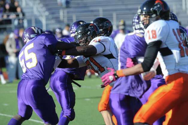 Stamford's Shaq Watkin and Weshill's Jon Carter collide as Westhill High School hosts Stamford High for a crosstown battle on the football field on Thanksgiving Day, November 24, 2011. Photo: Keelin Daly