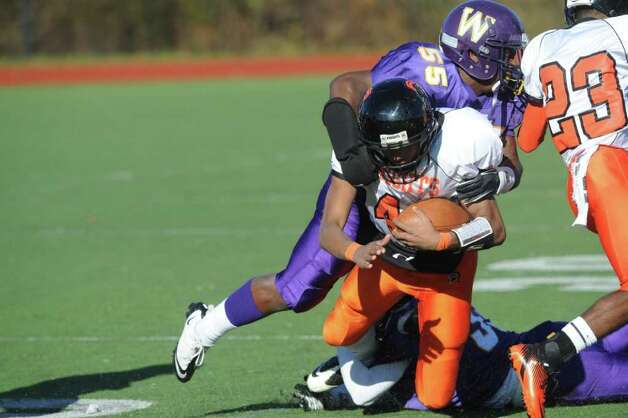 Westhill's Jon Carter stops Stamford's Bryan Boderick as Westhill High School hosts Stamford High for a crosstown battle on the football field on Thanksgiving Day, November 24, 2011. Photo: Keelin Daly