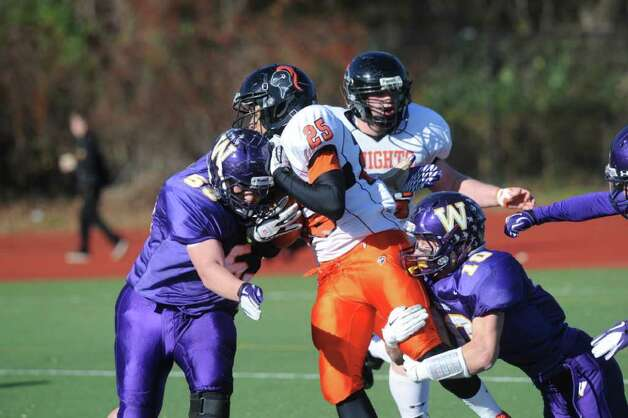 Stamford's Cameron Webb carries as Westhill's Chris Soule, left, James Irvine close in as Westhill High School hosts Stamford High for a crosstown battle on the football field on Thanksgiving Day, November 24, 2011. Photo: Keelin Daly