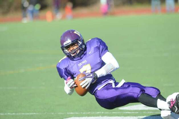 Westhill's Davell Cotterell pushes for yards as Westhill High School hosts Stamford High for a crosstown battle on the football field on Thanksgiving Day, November 24, 2011. Photo: Keelin Daly