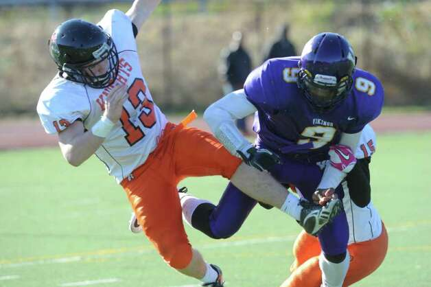 Stamford's Chandler Foster and Westhill's R.J. Cooper collide as Westhill High School hosts Stamford High for a crosstown battle on the football field on Thanksgiving Day, November 24, 2011. Photo: Keelin Daly