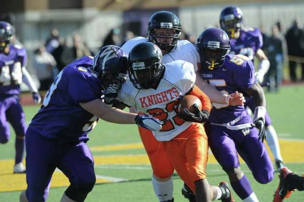 Stamford's Jamor Thompson pushes for yards as Westhill's Chris Soule resists as Westhill High School hosts Stamford High for a crosstown battle on the football field on Thanksgiving Day, November 24, 2011. Photo: Keelin Daly