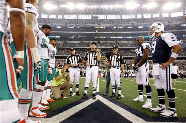 Referee Pete Morelli (135) flips the coin as the Dallas Cowboys and Miami Dolphins team captains look on before the start of an NFL football game Thursday, Nov. 24, 2011, in Arlington, Texas. (AP Photo/Sharon Ellman) Photo: Associated Press