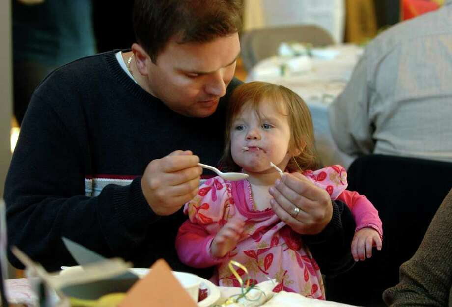 Mike Moon, of Westport, feed his daughter Sarah, 1, some turkey, at the annual Thanksgiving feast held at the Christ and Holy Trinity Episcopal Church in Westport, Conn. on Thursday November 24, 2011. The feast is usually held at nearby Saugatuck Congregational Church, but was moved because of a recent fire. Photo: Christian Abraham / Connecticut Post