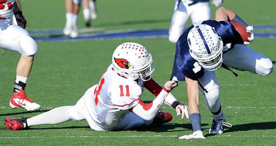 Alex McMurray # 11 of GHS takes down James Frusciante # 4 of Staples High School during the FCIAC Football Championship game in which Staples High School defeated Greenwich High School 31-27 at Staples, Westport, Thursday afternoon, Nov. 24, 2011. Photo: Bob Luckey / Greenwich Time