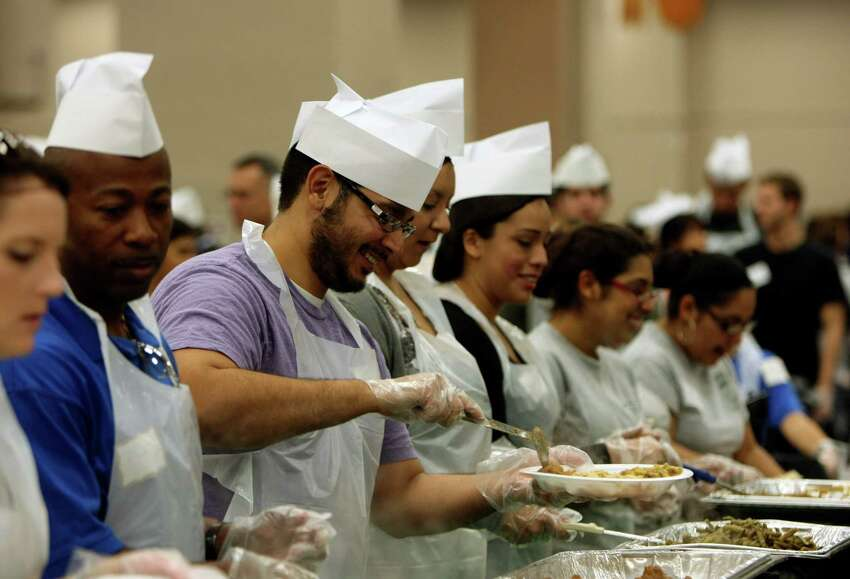 Volunteers prepare plates during the 32nd annual Raul Jimenez Thanksgiving Dinner, Nov. 24, 2011, at the Convention Center.