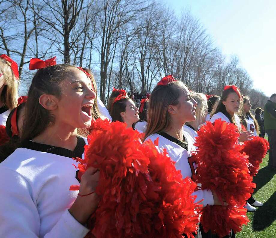 At left, GHS senior cheerleader Julia DeVico, 17, during the FCIAC Football Championship game in which Staples High School defeated Greenwich High School 31-27 at Staples, Westport, Thursday afternoon, Nov. 24, 2011. Photo: Bob Luckey / Greenwich Time