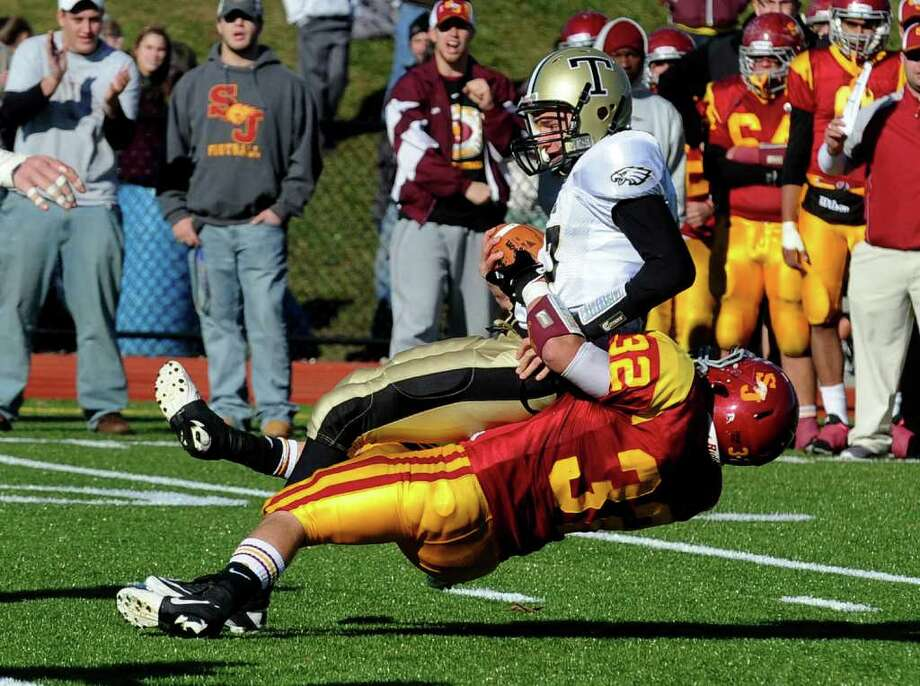 Trumbull QB #17 Nick Roberts is sacked by St. Joseph's #32 Mike Grasso, during Thanksgiving Day boys football action in Trumbull, Conn. on Thursday November 24, 2011. Photo: Christian Abraham / Connecticut Post