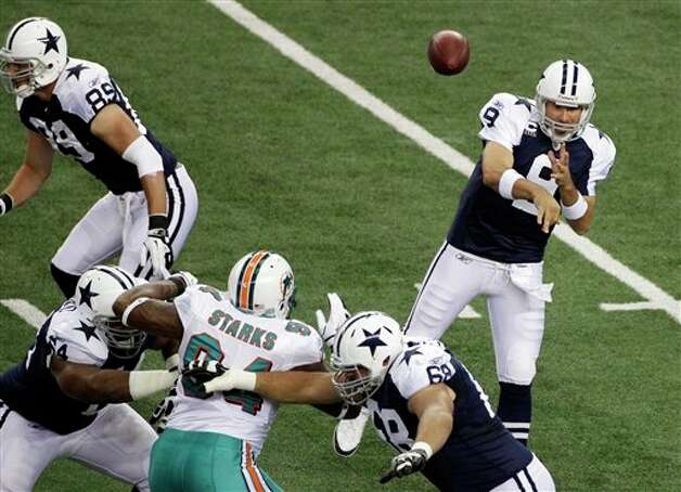 Dallas Cowboys quarterback Tony Romo (9) throws a pass as Miami Dolphins defensive end Randy Starks (94) pressures during the first quarter of an NFL football game, Thursday, Nov. 24, 2011, in Arlington, Texas. (AP Photo/Matt Strasen) Photo: Associated Press