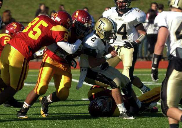 Highlights from Thanksgiving Day boys football action between St. Joseph and Trumbull in Trumbull, Conn. on Thursday November 24, 2011. Trumbull's #2 Ryan Pearson gets tackled by several St. Joe's players. Photo: Christian Abraham / Connecticut Post