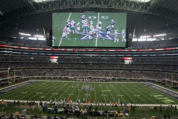 The large video screen shows the Dallas Cowboys and Miami Dolphins during the first half of an NFL football game Thursday, Nov. 24, 2011, in Arlington, Texas. (AP Photo/Matt Strasen) Photo: Associated Press