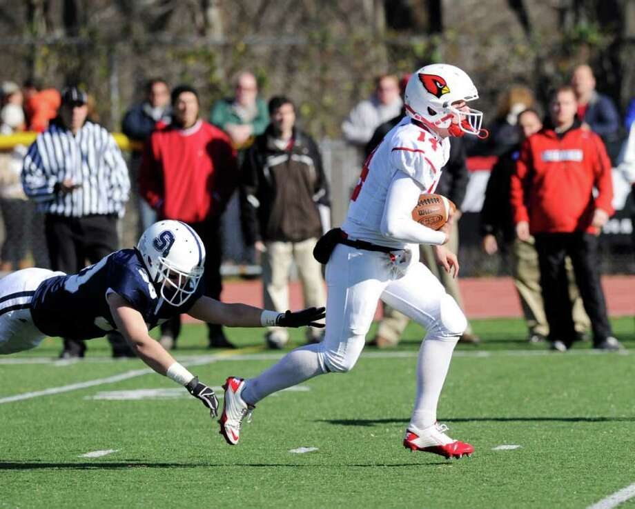 GHS QB Liam O'Neil, right, evades a diving Staples defender during the FCIAC Football Championship game in which Staples High School defeated Greenwich High School 31-27 at Staples, Westport, Thursday afternoon, Nov. 24, 2011. Photo: Bob Luckey / Greenwich Time