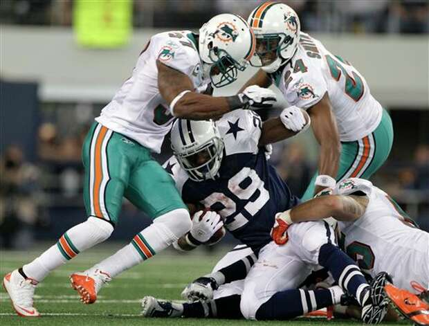 Miami Dolphins strong safety Yeremiah Bell, left, and cornerback Sean Smith (24) help to bring down Dallas Cowboys running back DeMarco Murray (29) on a short run in the first half of an NFL football game, Thursday, Nov. 24, 2011, in Arlington, Texas. (AP Photo/Matt Strasen) Photo: Associated Press