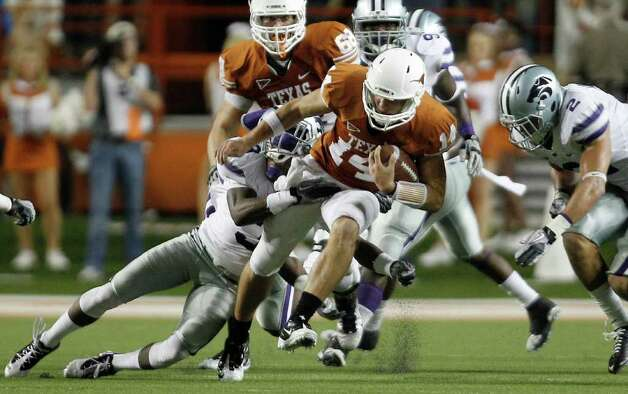 Texas' David Ash (14) is stopped by  Kansas State's Allen Chapman, left,  during the second quarter of an NCAA college football game, Saturday, Nov. 19, 2011, in Austin, Texas. Photo: AP