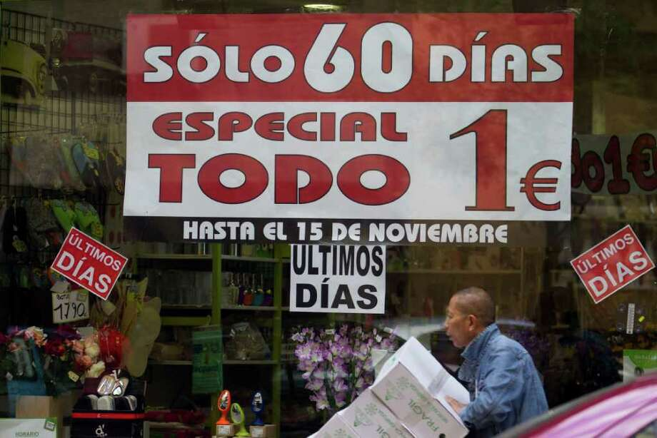 PAUL WHITE : ASSOCIATED PRESS IT'S SPECIAL: A worker takes in items to a store selling household goods for only 1 euro in Madrid. Everyday Europeans have expressed appreciation for the economic benefits the currency has brought, despite the continent's economic woes, and they fear what would unfold were the euro zone to break up. Photo: Paul White / AP