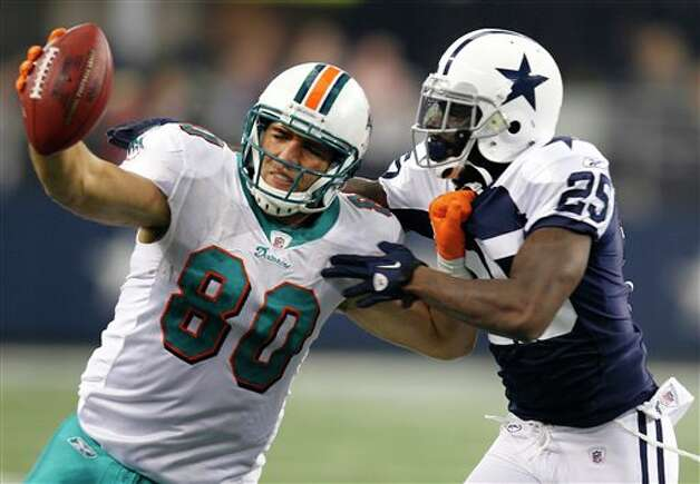 Miami Dolphins tight end Anthony Fasano (80) fights for yardage as Dallas Cowboys defensive back Frank Walker (25) chases him down in the first half of an NFL football game, Thursday, Nov. 24, 2011, in Arlington, Texas. (AP Photo/Sharon Ellman) Photo: Associated Press