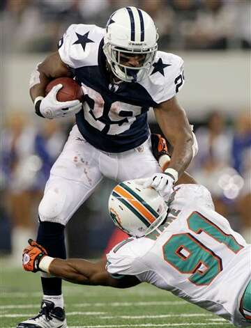 Dallas Cowboys running back DeMarco Murray (29) fights off a tackle attempt by Miami Dolphins outside linebacker Cameron Wake (91) in the first half of an NFL football game, Thursday, Nov. 24, 2011, in Arlington, Texas. (AP Photo/Matt Strasen) Photo: Associated Press