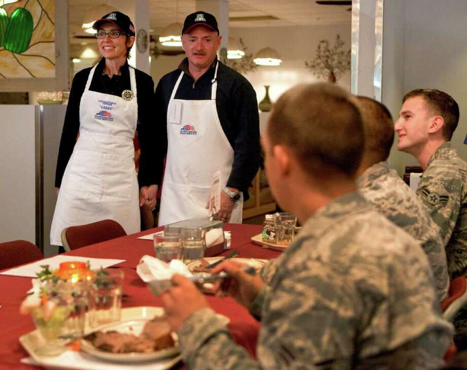 PREMIUM CONTENT--HIGHER RATES APPLY FOR NON-PHOTOSTREAM MEMBERS - U.S. Rep Gabrielle Giffords, D-Ariz., and her husband, retired Capt. Mark Kelly, meet both active and retired airmen after serving a Thanksgiving meal to troops at Davis-Monthan Air Force Base, Thursday, Nov. 24, 2011, in Tucson, Ariz. (AP Photo/Matt York) Photo: Matt York / AP