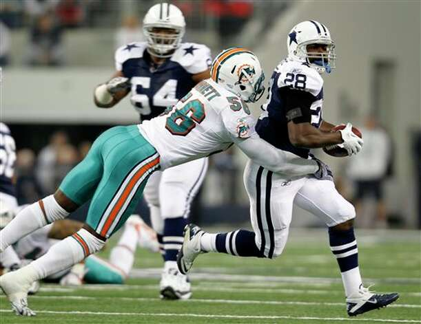 Dallas Cowboys running back Felix Jones (28) attempts to evade Miami Dolphins inside linebacker Kevin Burnett (56) in the first half of an NFL football game, Thursday, Nov. 24, 2011, in Arlington, Texas. (AP Photo/Sharon Ellman) Photo: Associated Press