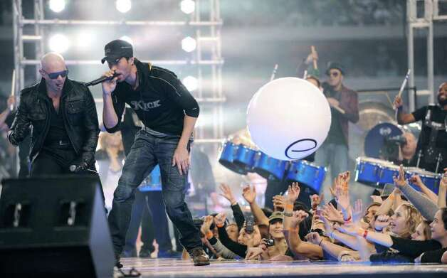 Entertainers Pitbull, left, and Enrique Iglesias perform during halftime of the Miami Dolphins at Dallas Cowboys NFL game at Cowboys Stadium on Thanksgiving Day, Nov. 24, 2011. BILLY CALZADA / gcalzada@express-news.net