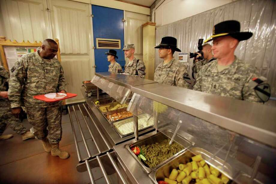 U.S. soldiers serve Thanksgiving meal for Gen. Lloyd Austin, left, the top U.S. commander in Iraq at Contingency Operating Site Echo, in Diwaniyah, 120 kilometers (80 miles) south of Baghdad, Iraq, Thursday, Nov. 24, 2011. The U.S. has promised to withdraw from Iraq by the end of the year as required by a 2008 security agreement between Washington and Baghdad. A little less than 20,000 U.S. troops are scheduled to clear out along with their equipment. (AP Photo/Khalid Mohammed) Photo: Khalid Mohammed / AP