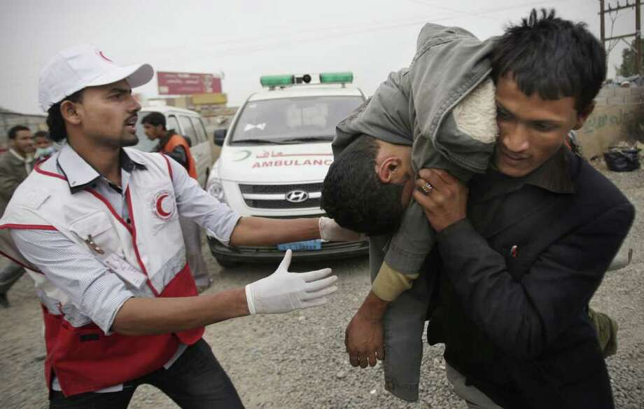 A man carries a wounded protester during clashes with security forces in Sanaa, Yemen, Thursday, Nov. 24, 2011. A medic at a field hospital in Sanaa says several people have been killed by security forces and regime supporters who fired upon crowds demanding that President Ali Abdullah Saleh be put on trial. (AP Photo/Hani Mohammed) Photo: Hani Mohammed / AP