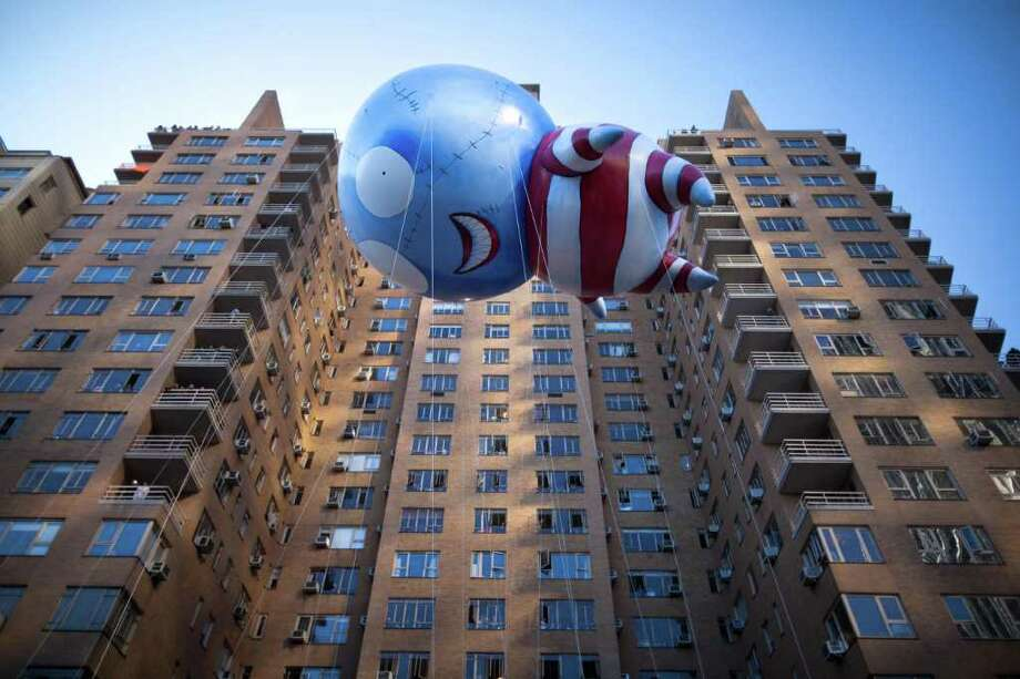 Filmmaker Tim Burton's B floats along 59th Street during Macy's Thanksgiving Day Parade, Thursday, Nov. 24, 2011, in New York. A jetpack-wearing monkey and Burton's freakish creation are two of the big new balloons that will make their inaugural appearances in front of millions of people at this year's parade. (AP Photo/John Minchillo) Photo: John Minchillo / FR170537 AP
