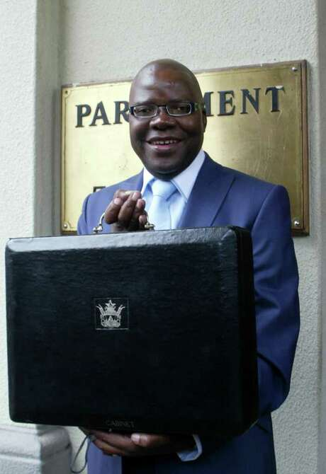 Zimbabwe's Finance Minister Tendai Biti poses with a briefcase carrying the country's national 2011 budget as he arrives to present it before the Parliament in Harare on November 24, 2011. Zimbabwean government expects to take in $600 million in additional revenue from diamond sales next year, after a global watchdog lifted its ban on exports.    AFP PHOTO / Jekesai Njikizana. (Photo credit should read JEKESAI NJIKIZANA/AFP/Getty Images) Photo: JEKESAI NJIKIZANA / AFP