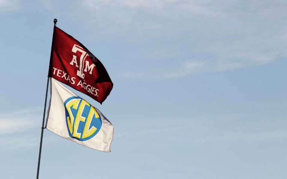 Texas A&M and Southeastern Conference flags fly over the tailgating area before an NCAA college foot