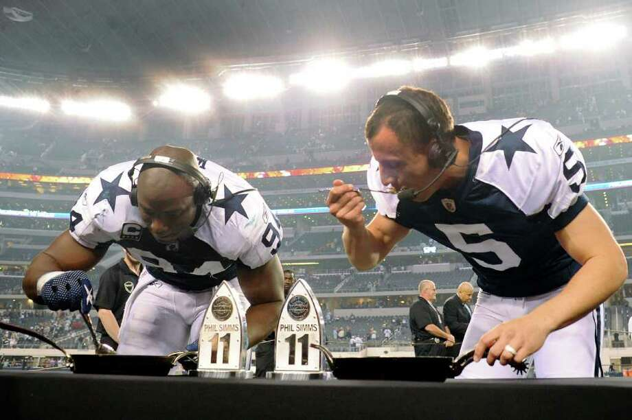 Dallas Cowboys players DeMarcus Ware, left, and Dan Bailey eat cobbler after being chosen as players of the game against Miami at Cowboys Stadium on Thanksgiving Day, Nov. 24, 2011. BILLY CALZADA / gcalzada@express-news.net