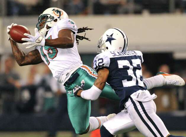 Miami receiver Davone Bess hauls in a pass as Dallas defender Orlando Scandrick chases during second-half NFL action at Cowboys Stadium on Thanksgiving Day, Nov. 24, 2011. BILLY CALZADA / gcalzada@express-news.net