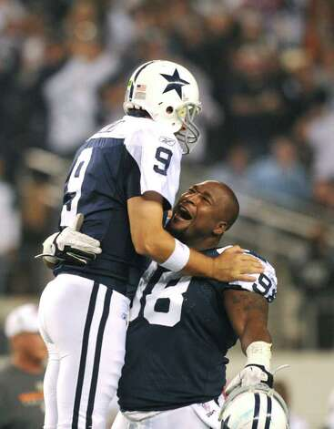 Dallas Cowboys' quarterback Tony Romo (9) is congratulated by teammate Marcus Spears after the Cowboys' defeated the Miami Dolphins, 20-10, in Thanksgiving Day NFL action at Cowboys Stadium on Nov. 24, 2011. BILLY CALZADA / gcalzada@express-news.net