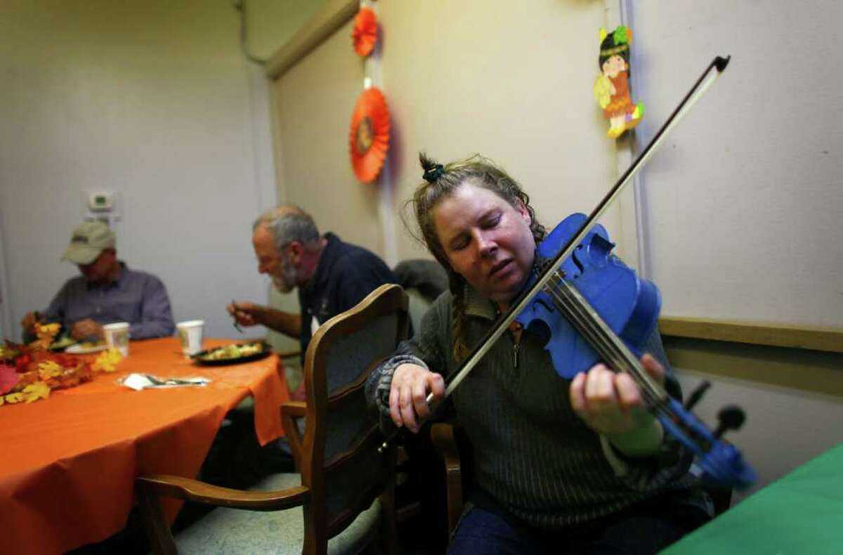 Shelter resident Martha Weiss plays her violin after eating dinner at the new Union Gospel Mission winter shelter at the old Fire Station 39 in Lake City on Thursday, November 24, 2011. The shelter started operations in the shuttered fire station on Thanksgiving Day.