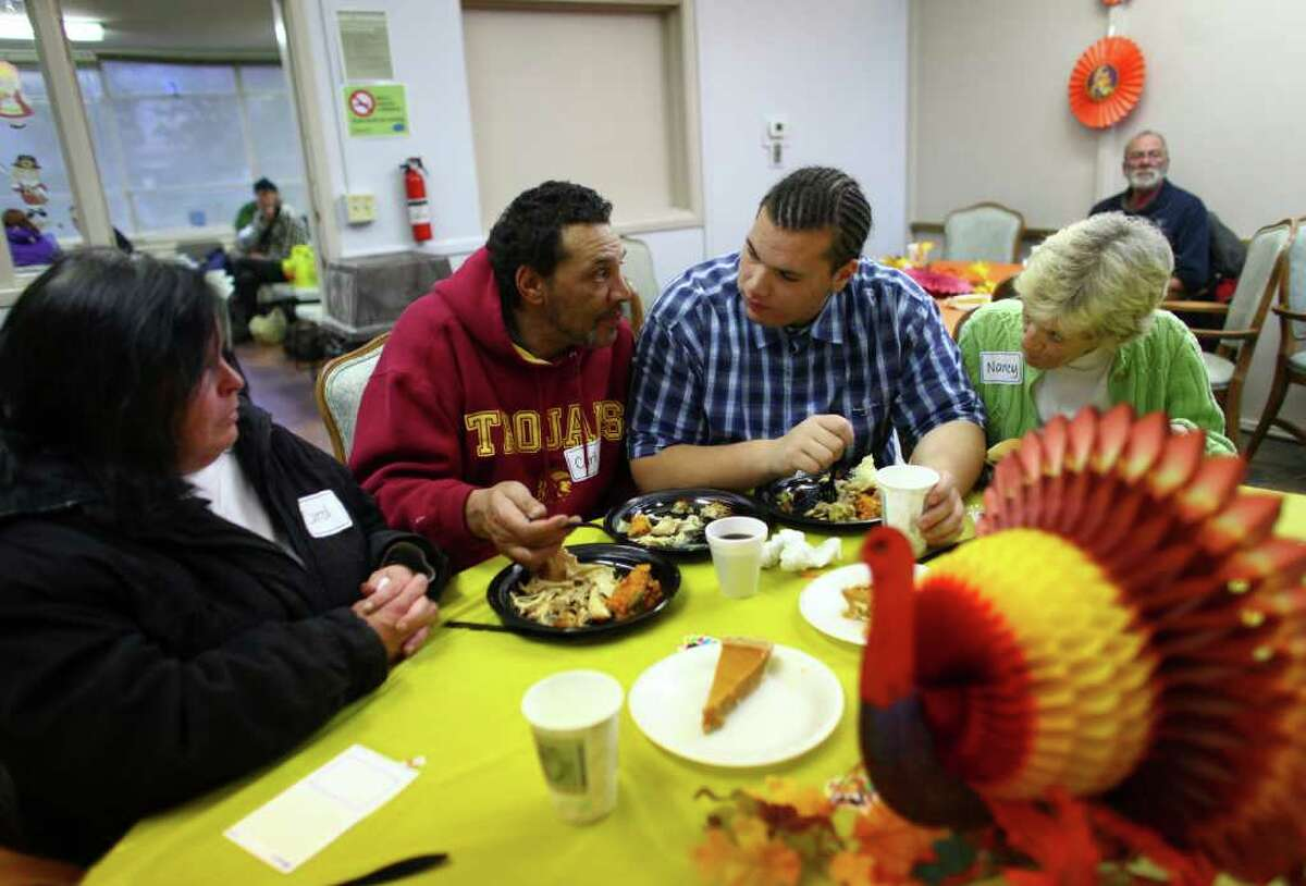 Kam Johnson, center right of Lynnwood, visits his dad Carl Johnson at the new Union Gospel Mission winter shelter at the old Fire Station 39 in Lake City on Thursday, November 24, 2011. The shelter started operations in the shuttered fire station on Thanksgiving Day.