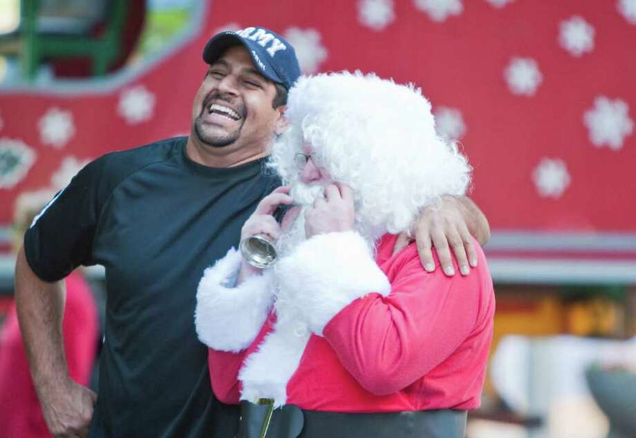 Raj Sharma, a Thanksgiving Superfeast committee member, laughs with Santa, Greg Beard, as Santa visits the Farmer's Market Downtown, Wednesday, Nov. 23, 2011, outside City Hall in Houston. Photo: Nick De La Torre, Houston Chronicle / © 2011  Houston Chronicle