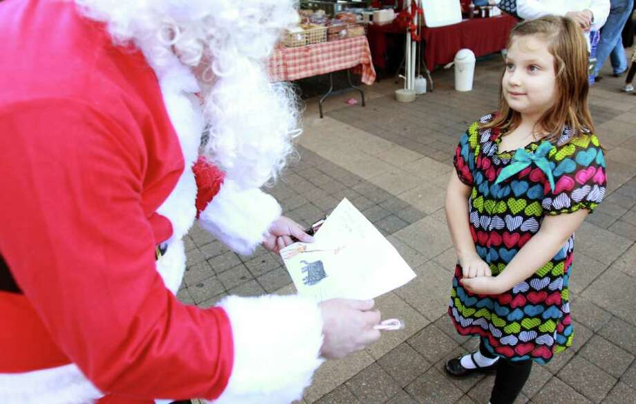 Morgan Salguero, 7, right, gives Santa, Greg Beard, a picture she drew for him as Santa visits the Farmer's Market Downtown. Photo: Nick De La Torre, Houston Chronicle / © 2011  Houston Chronicle