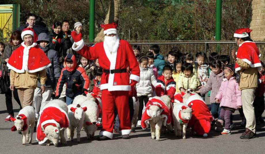 An amusement park employee dressed as Santa Claus walks sheep in the same costumes at the Everland amusement park during an event to celebrate Christmas in Yongin, South Korea. Christmas is one of the biggest holidays celebrated in the country with over half the population being Christians. Photo: Ahn Young-joon, Associated Press / AP