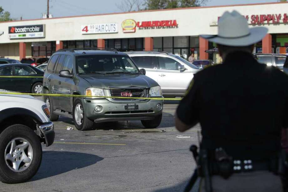 MELISSA PHILLIP :CHRONICLE  POSSIBLY GANG-RELATED: Police cordon off an SUV after its driver was  shot  through the front windshield Thursday in a shopping center parking lot at the corner of Airline and West Road. Photo: Melissa Phillip / © 2011 Houston Chronicle