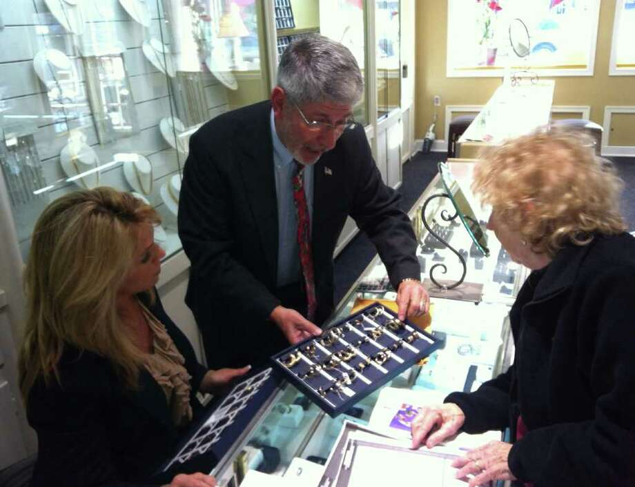 Howard Diamond, co-owner of Fairfield Center Jewelers, center, and sales associate Kim Vance, left, show some jewelry to Naomi Fixman-Byrne, a patron from Stratford. Diamond said he hopes his store will have the same or better revenues this holiday season compared to last year. Photo: Michael C. Juliano/Staff Photo