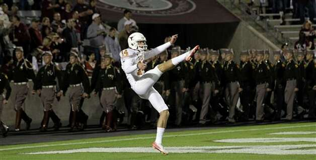 Texas kicker William Russ (14) warms up as members of the Texas A&M Corps of Cadets march into the stadium before an NCAA college football game, Thursday, Nov. 24, 2011, in College Station, Texas. (AP Photo/David J. Phillip) Photo: Associated Press