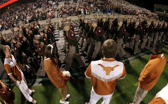 Texas cheerleaders watch as members of the Texas A&M Corps of Cadets march into the stadium before an NCAA college football game, Thursday, Nov. 24, 2011, in College Station, Texas. (AP Photo/David J. Phillip) Photo: Associated Press