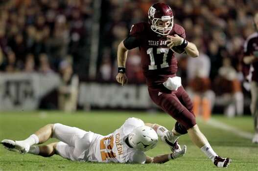 Texas A&M quarterback Ryan Tannehill (17) eludes the tackle of Texas safety Blake Gideon (21) during the first quarter of an NCAA college football game, Thursday, Nov. 24, 2011, in College Station, Texas. (AP Photo/David J. Phillip) Photo: Associated Press